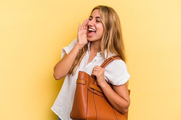 Jeune femme blonde caucasienne portant un sac en cuir isolé sur fond jaune criant et tenant la paume près de la bouche ouverte.
