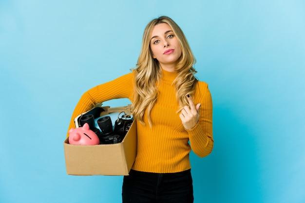 Jeune femme blonde caucasienne tenant des boîtes pour se déplacer en pointant avec le doigt sur vous comme si vous invitiez à vous rapprocher.