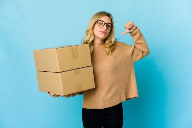 Jeune femme blonde caucasienne tenant des boîtes pour se déplacer se sent fière et confiante, exemple à suivre.