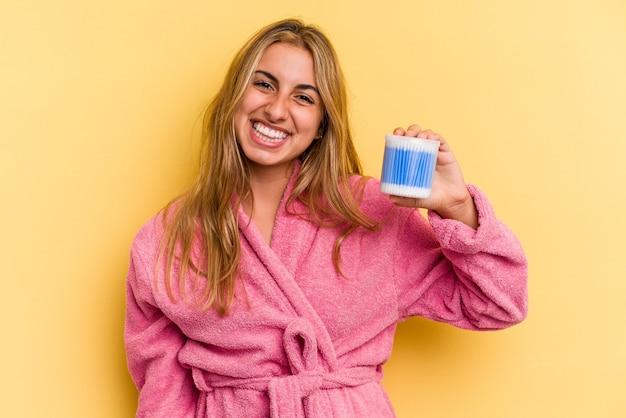 Jeune femme blonde caucasienne tenant des cotons-tiges isolés sur fond jaune heureux, souriant et joyeux.
