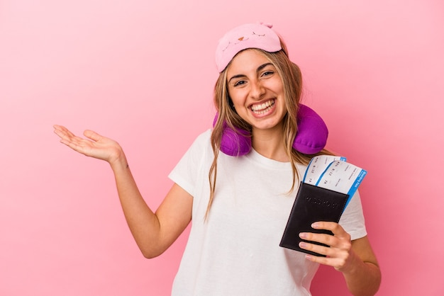 Jeune femme blonde caucasienne tenant un passeport et des billets pour voyager isolé sur fond rose montrant un espace de copie sur une paume et tenant une autre main sur la taille.