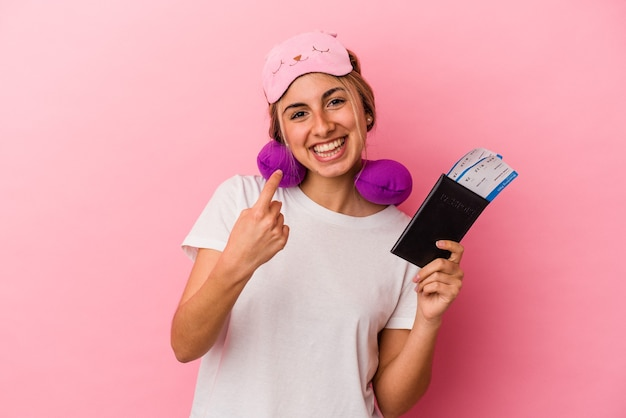 Jeune femme blonde caucasienne tenant un passeport et des billets pour voyager isolé sur fond rose pointant avec le doigt sur vous comme si vous invitiez à vous rapprocher.