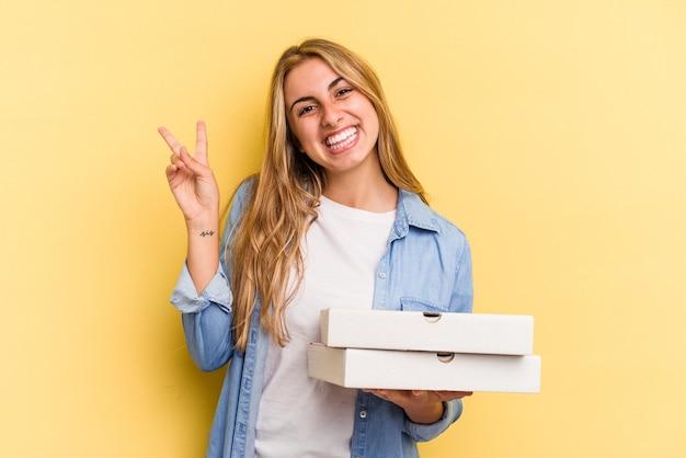 Jeune femme blonde caucasienne tenant des pizzas isolées sur fond jaune joyeuse et insouciante montrant un symbole de paix avec les doigts.