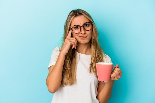 Jeune femme blonde caucasienne tenant une tasse isolée sur fond bleu pointant le temple avec le doigt, pensant, concentré sur une tâche.