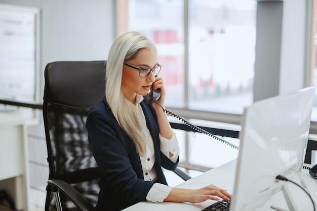 Jeune femme blonde caucasienne en tenue de soirée et avec des lunettes tapant sur le clavier et ayant un appel téléphonique assis dans le bureau. chaque jour est un nouveau jour. traitez-le de cette façon.