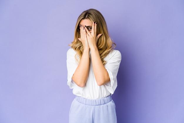 Jeune femme blonde cligner des yeux à travers les doigts effrayés et nerveux