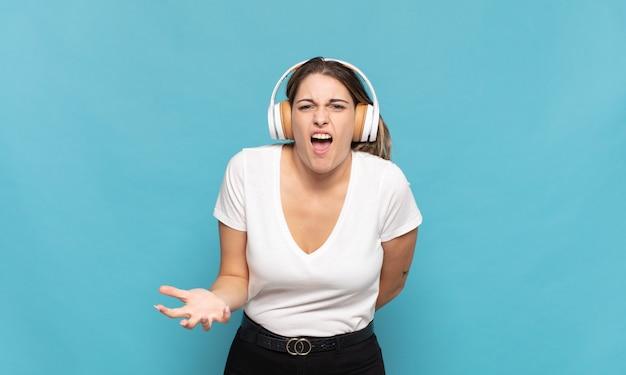 Jeune femme blonde à la colère, agacé et frustré crier wtf