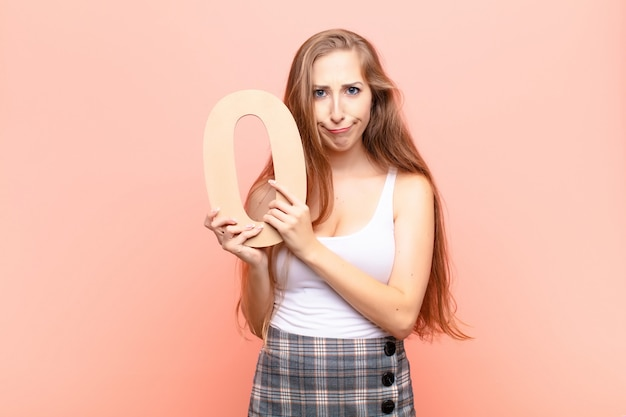 Jeune femme blonde en colère, colère, désaccord, tenant un numéro 0