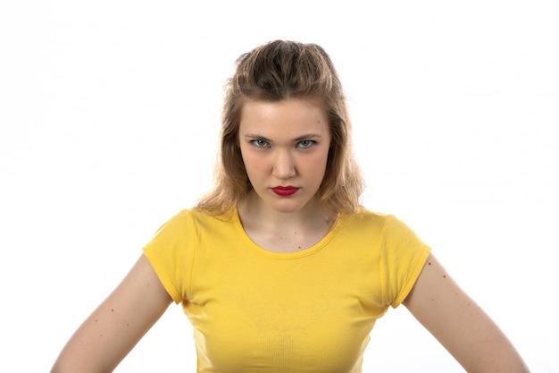 Jeune femme blonde en colère avec un t-shirt jaune