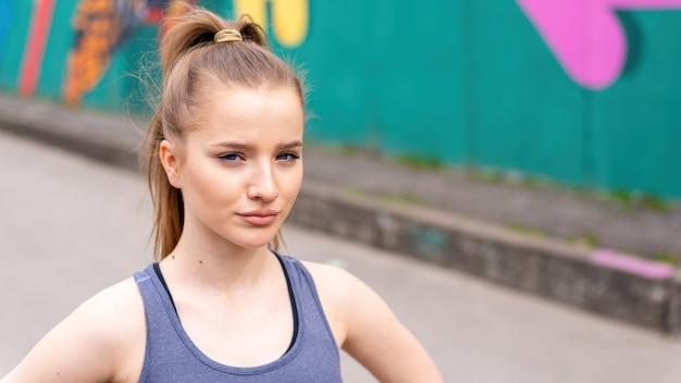 Jeune femme blonde concentrée dans les vêtements de sport à la formation en plein air, fond multicolore