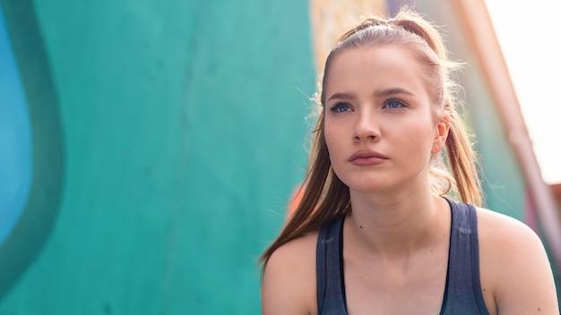 Jeune femme blonde concentrée à la formation en plein air se préparant à commencer à courir, fond multicolore