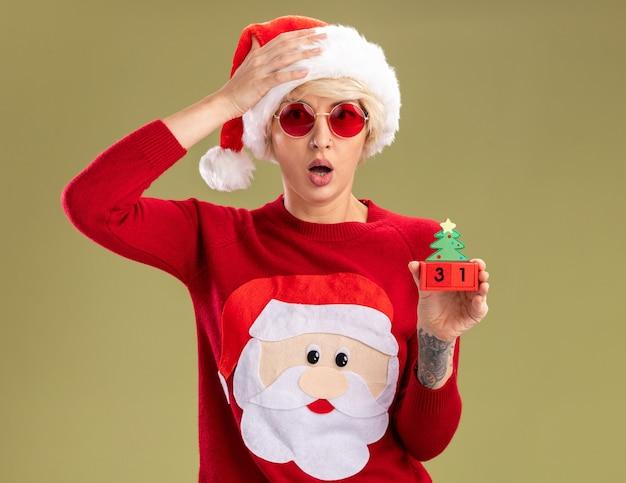 Jeune femme blonde concernée portant un chapeau de noël et un pull de noël du père noël avec des lunettes tenant un jouet d'arbre de noël avec une date regardant en gardant la main sur la tête isolée sur un mur vert olive