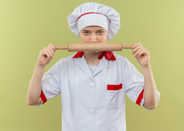 Jeune femme blonde confiante chef en uniforme de chef détient un rouleau à pâtisserie et semble isolé sur un mur vert