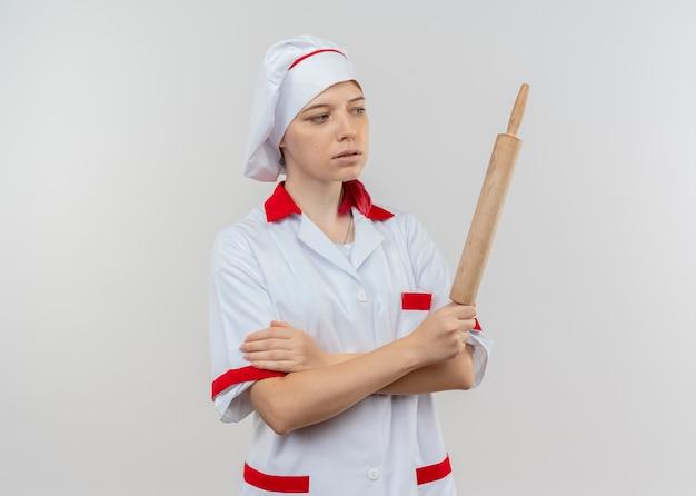 Jeune femme blonde confiante chef en uniforme de chef tient et regarde rouleau à pâtisserie isolé sur mur blanc