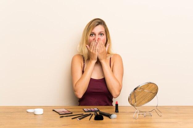 Jeune femme blonde avec des cosmétiques dans un tableau avec une expression faciale surprise