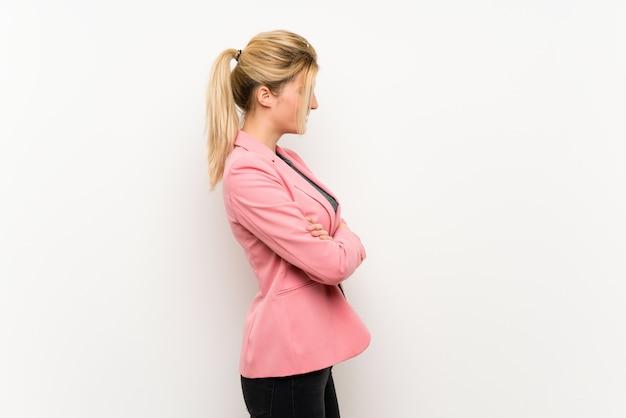 Jeune femme blonde avec un costume rose en position latérale