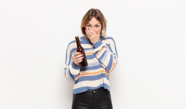 Jeune femme blonde couvrant la bouche avec les mains avec une expression choquée et surprise, gardant un secret ou disant oups