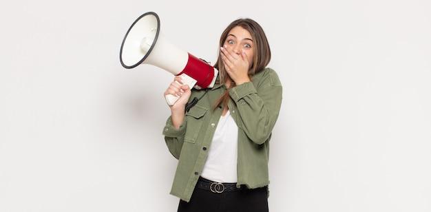 Jeune femme blonde couvrant la bouche avec les mains avec une expression choquée et surprise, en gardant un secret ou en disant oups