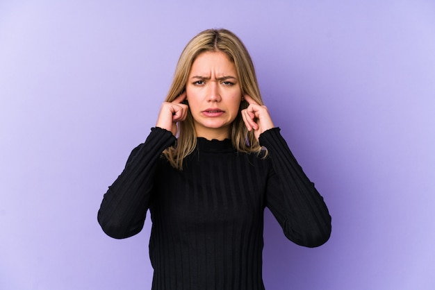 Jeune femme blonde couvrant les oreilles avec les doigts, stressée et désespérée par une forte ambiance