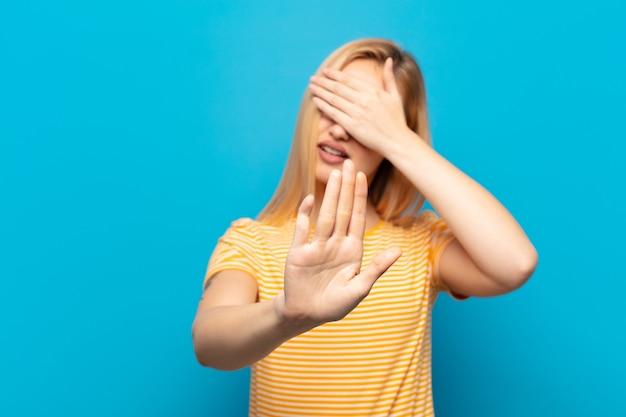 Jeune femme blonde couvrant le visage avec la main et mettant l'autre main devant pour arrêter l'appareil photo, refusant des photos ou des images