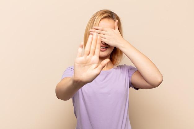 Jeune femme blonde couvrant le visage avec la main et mettant l'autre main devant pour s'arrêter, refusant des photos ou des images