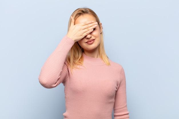 Jeune Femme Blonde Couvrant Les Yeux D'une Main Se Sentant Effrayé Ou Anxieux, Se Demandant Ou Attendant Aveuglément Une Surprise Photo Premium