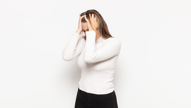 Jeune femme blonde couvrant les yeux avec les mains avec un regard triste et frustré de désespoir, de pleurs, de vue latérale