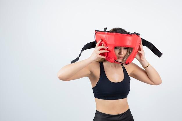 Jeune femme blonde en crop top portant un casque de boxe rouge.
