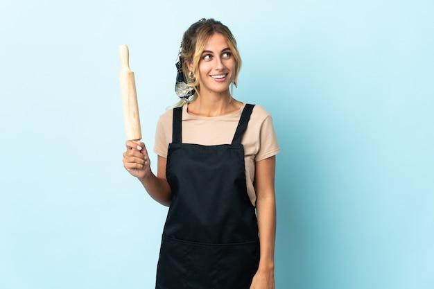 Jeune femme blonde de cuisine uruguayenne sur bleu pensant une idée tout en regardant