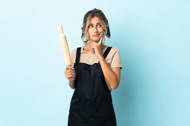 Jeune femme blonde cuisine uruguayenne isolée sur bleu ayant des doutes et de la pensée