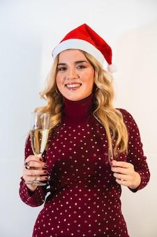 Jeune femme blonde dans un bonnet de noel faisant un toast de fête