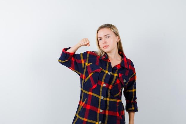 Jeune femme blonde dans une chemise à carreaux