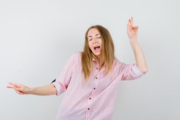 Jeune femme blonde dans une chemise rose décontractée