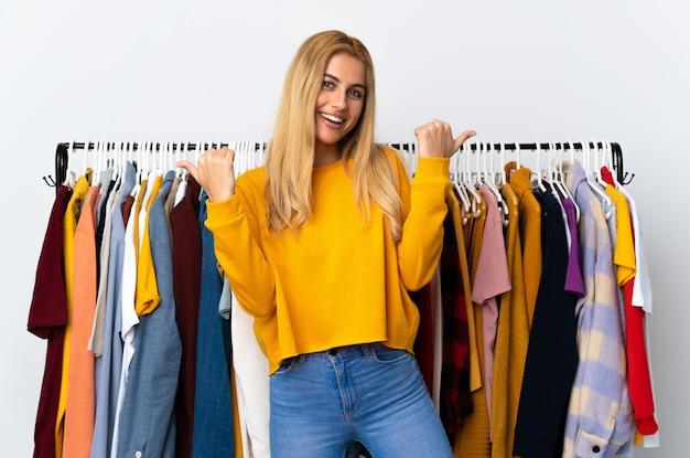 Jeune femme blonde dans un magasin de vêtements avec le geste du pouce en l'air et souriant