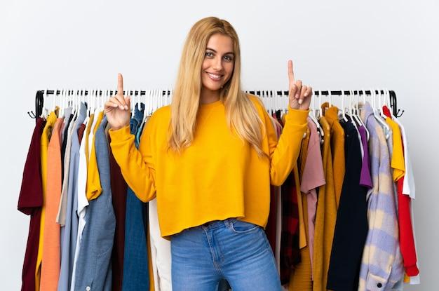 Jeune femme blonde dans un magasin de vêtements pointant vers le haut une bonne idée