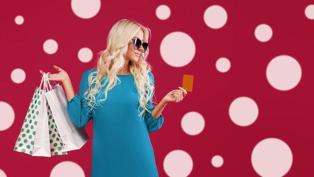 Une jeune femme blonde dans une robe verte tient des paquets et une carte de crédit.