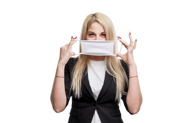 Jeune femme blonde dans une veste met un masque. pandémie de coronavirus. isolé sur un mur blanc.