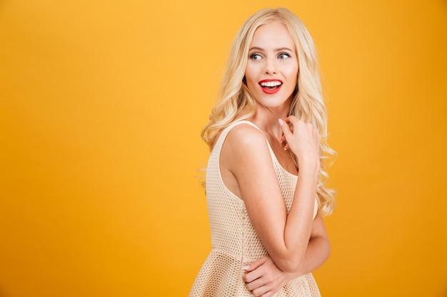 Jeune femme blonde debout isolé sur jaune