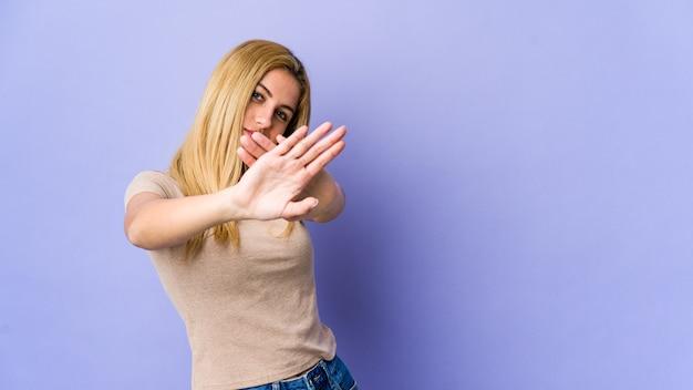 Jeune femme blonde debout avec la main tendue montrant le panneau d'arrêt, vous empêchant.
