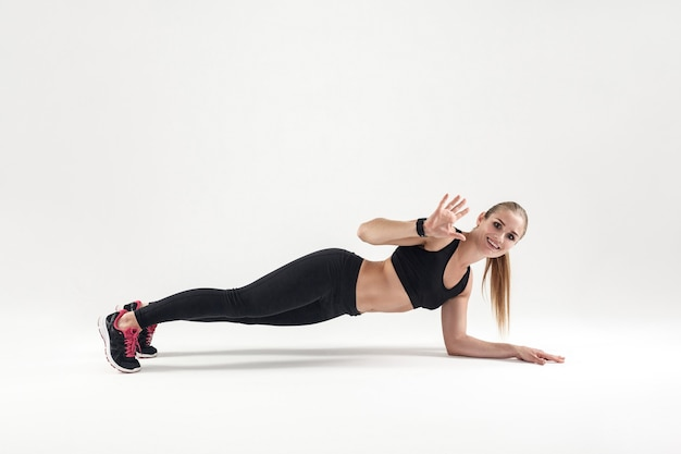 Jeune femme blonde debout en planche studio shot