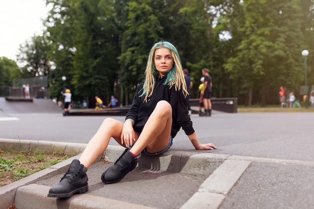Jeune femme blonde avec des dreadlocks assis sur le skate park