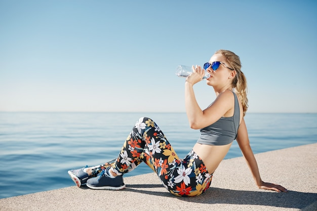 Jeune femme blonde eau potable après avoir couru à la plage