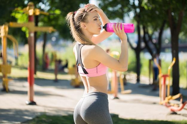 Jeune femme blonde eau potable pendant le jogging du matin