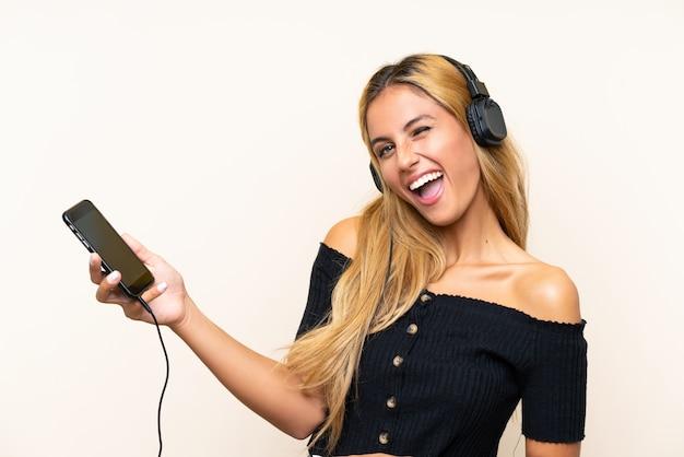 Jeune femme blonde écoute de la musique avec un téléphone portable et chante sur un mur isolé
