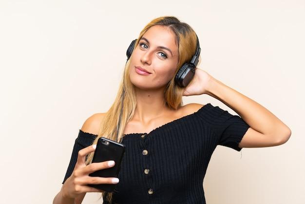 Jeune femme blonde écoute de la musique avec un téléphone portable