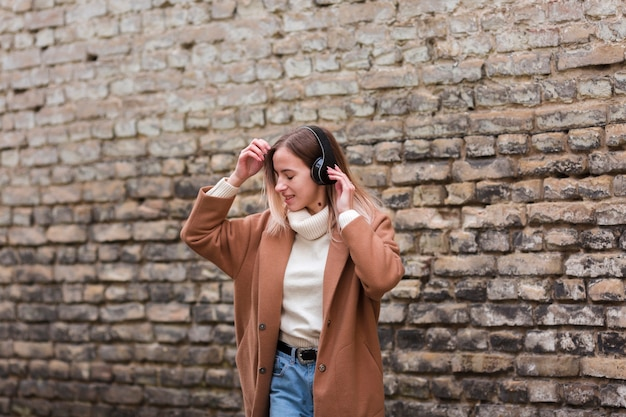 Jeune femme blonde, écouter de la musique sur les écouteurs