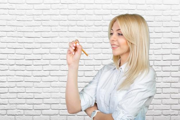 Jeune femme blonde écrivant sur l'écran tactile