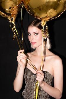 Jeune femme blonde élégante avec des ballons de couleur dorée bénéficiant d'une fête d'anniversaire ou d'un autre événement de célébration sur fond noir