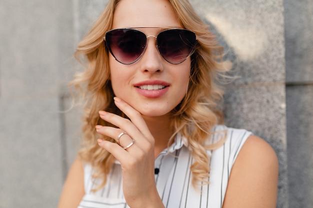 Jeune femme blonde élégante et séduisante marchant dans la rue de la ville en robe de style mode d'été portant des lunettes de soleil