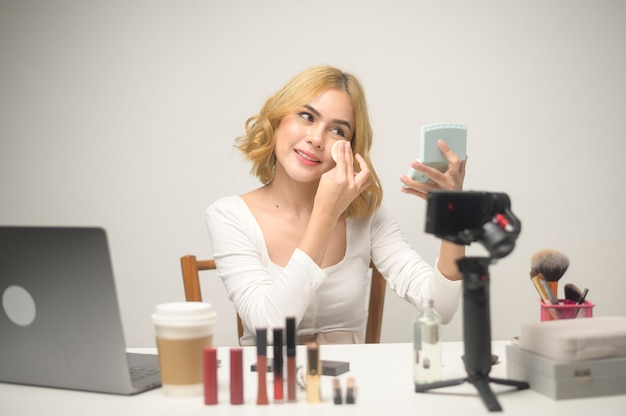 Une jeune femme blonde entrepreneur travaillant avec un ordinateur portable présente des produits cosmétiques au cours de la diffusion en direct en ligne sur fond blanc studio, vente en ligne et concept de blogueur de beauté